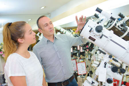 eyepiece: Salesman showing telescope to young female customer Stock Photo