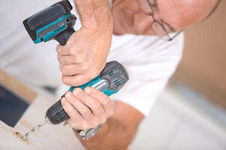 a drill: Carpenter using a cordless drill