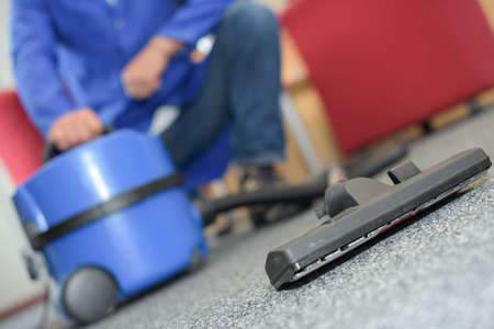 empty office: Closeup of man crouching by vacuum cleaner Stock Photo