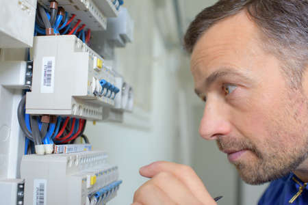 manual measuring instrument: Inspecting a faulty fusebox Stock Photo