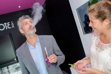 vapour: Man trying an electronic cigarette, breathing out vapour