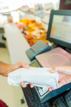 shop tender: Butcher handing wrapped meat to customer