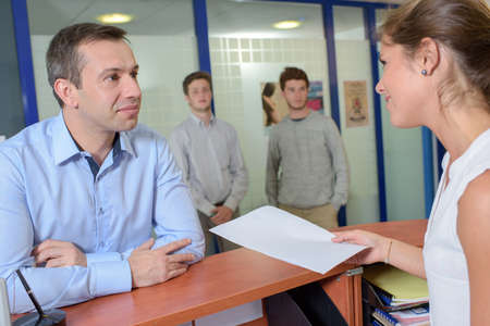 greet eyes: Lady handing form to man at reception desk Stock Photo