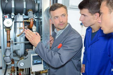 explaining: Man explaining machinery to trainees