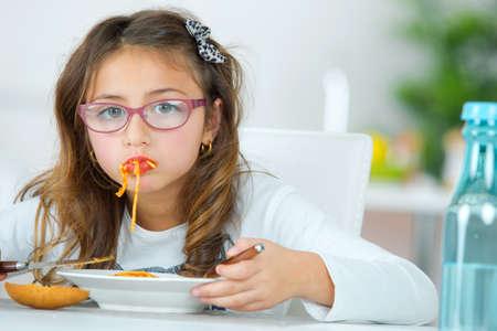 niña comiendo: Little girl eating spaghetti at home