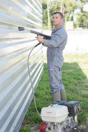 machine à laver: Homme utilisant nettoyeur haute pression