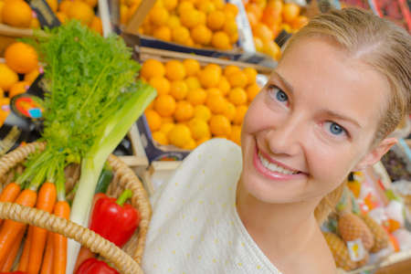 grocers: Woman showing basket of vegetables Stock Photo