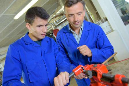 bar tool set: Teacher encouraging apprentice using machinery