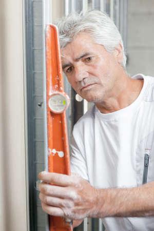 angled: Builder holding angled spirit level to wall