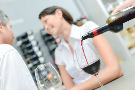 Pouring red wine for couple on a date