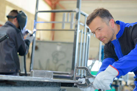 industrious: Two workmen busy in workshop Stock Photo