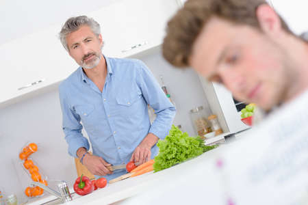 man holding book: Man cooking, looking towards younger man holding book Stock Photo