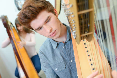 Teenager playing the harp Stock Photo