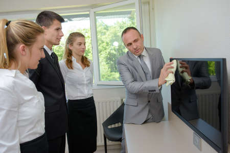 new recruits: Trainee cleaners watching supervisor clean television screen