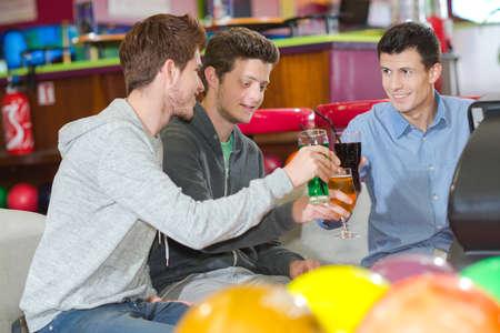 three men with drinks