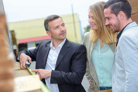 prove: Salesman measuring building materials for couple Stock Photo