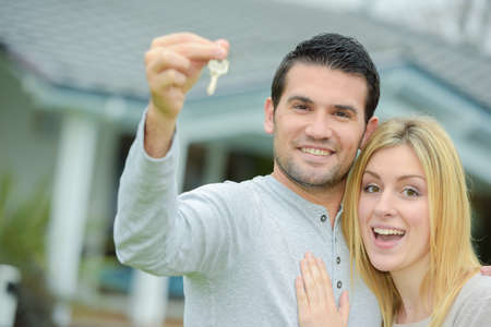Couple holding keys to their new house