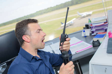 receiver: Man in control tower shouting into radio receiver