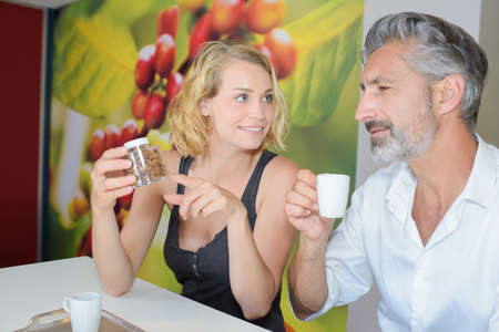 origin of man: Lady pointing to coffee beans as man drinks