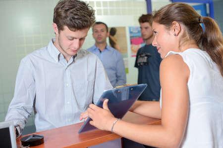 cabizbajo: Señora que muestra el portapapeles al hombre joven Foto de archivo