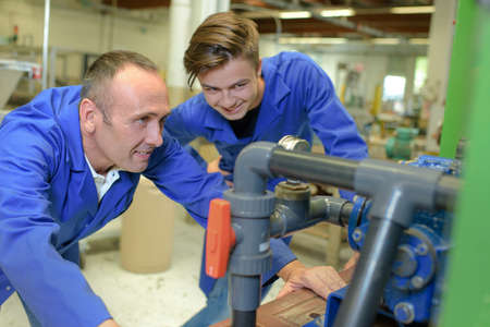 operative: Man and apprentice looking at machinery Stock Photo
