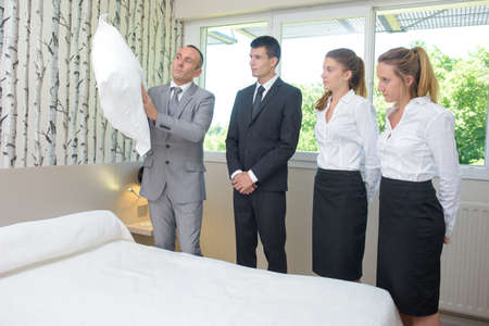 hotel staff: Hotel staff watching supervisor with pillow