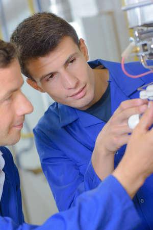 Des hommes travaillant sur des câblages Banque d'images - 61778588