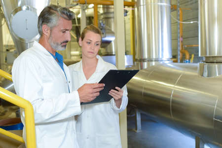 confer: Man and woman looking at clipboard, stood next to metal vat