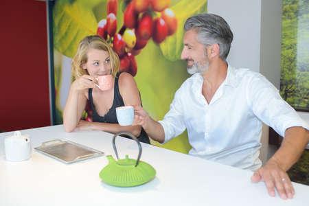 hombre sentado: hombre sentado y señora con bebidas calientes