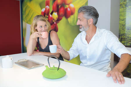 hombre sentado: Seated man and lady with hot drinks Foto de archivo