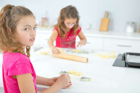 two children: Two children making biscuits Stock Photo