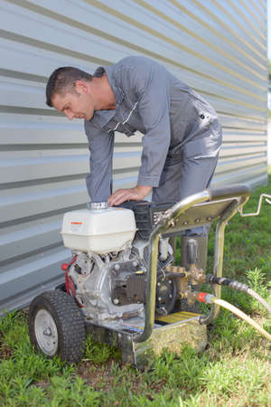 lean machine: Man leaning over generator