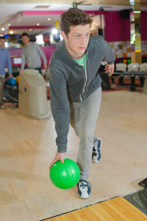 poised: Young man poised to throw bowling ball