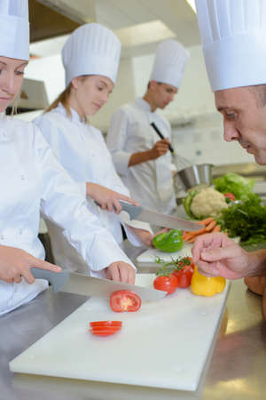 Chef watching students chop vegetables Stock Photo