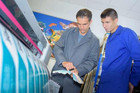 Twee mensen controleren van de kleur van drukwerken Stockfoto