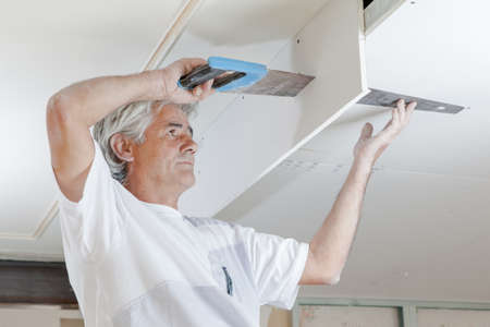ceiling: Sawing a ceiling panel Stock Photo