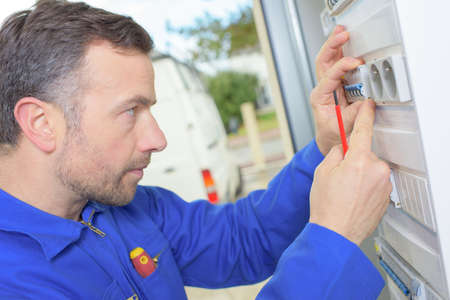 fusebox: Electrician inspecting a fusebox Stock Photo