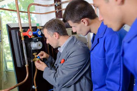 cobre: Profesor con los estudiantes a trabajar en las tuberías de cobre Foto de archivo