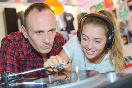 record: Man watching young lady putting vinyl record playing