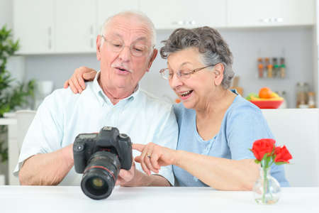 Elderly couple looking at photographs on back of  digital camera Stock Photo