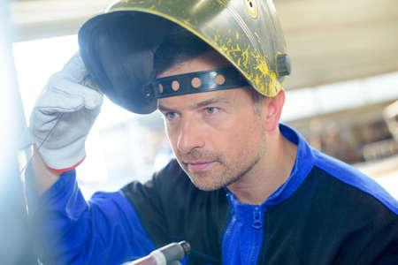 welding mask: Man lifting welding mask Stock Photo