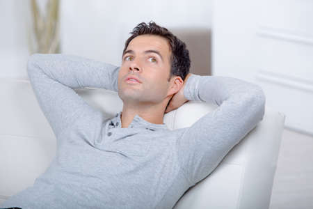laying down: Man relaxing on his sofa