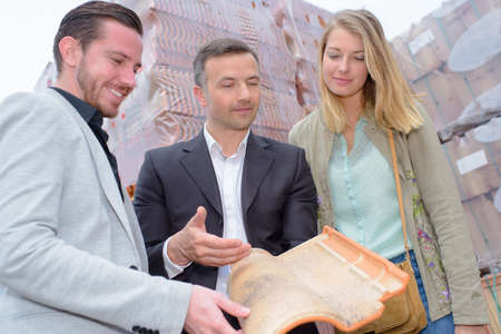 nonslip: Salesman holding a modern rooftile for couple to see