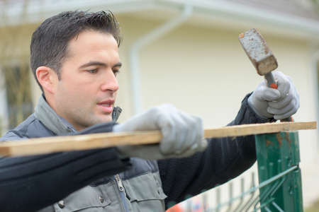 Hammering a fence into place Stock Photo