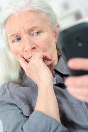 persona de la tercera edad: Mayor que lee un mensaje de texto dama