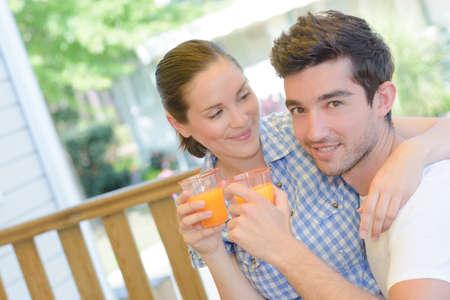 amorous: Amorous couple with glasses of juice Stock Photo