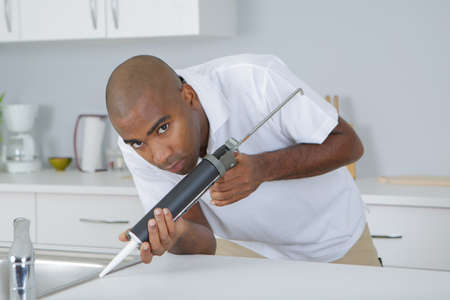 sealant: Man using sealant gun