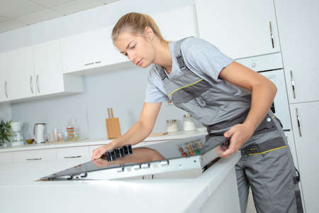 fitter: Woman fitting ceramic hob into kitchen