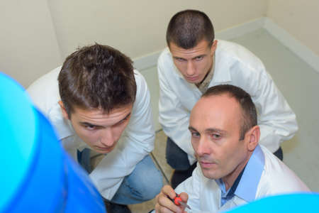 vocational high school: three men doing an inspection Stock Photo