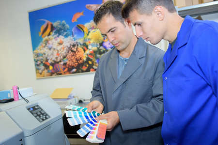 confer: Two male workers looking at colour charts